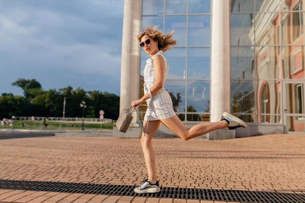 サングラスとハンドバッグを身に着けている夏のファッションスタイルの白いドレスで街の通りのスニーカーで面白いジャンプを実行している若い魅力的なスタイリッシュな女性