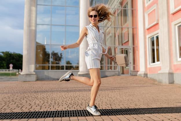 Giovane donna alla moda attraente in esecuzione saltando divertente in scarpe da ginnastica in strada cittadina in abito bianco stile moda estate indossando occhiali da sole e borsa