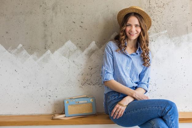壁に座っている若い魅力的なスタイリッシュな女性