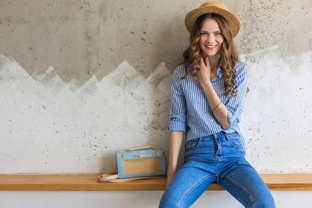 Giovane donna alla moda attraente che si siede alla parete