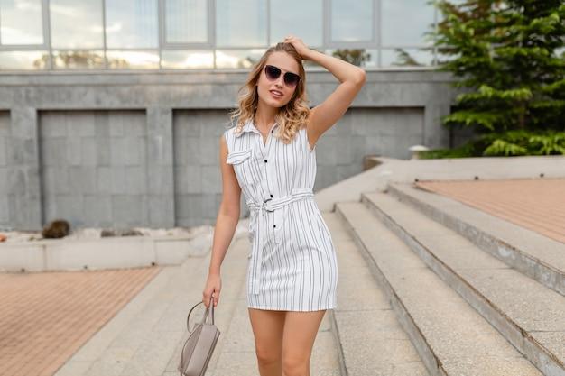 Giovane donna alla moda attraente con l'acconciatura riccia bionda che cammina nella via della città in vestito a strisce bianco di stile di modo di estate che indossa occhiali da sole che tengono la borsa