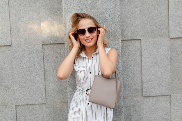 Young attractive stylish woman with blond curly hairstyle walking in city street in summer fashion style white striped dress wearing sunglasses holding purse
