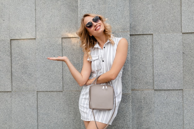 財布を保持しているサングラスを身に着けている夏のファッションスタイルの白い縞模様のドレスで街を歩く金髪の巻き毛の髪型を持つ若い魅力的なスタイリッシュな女性