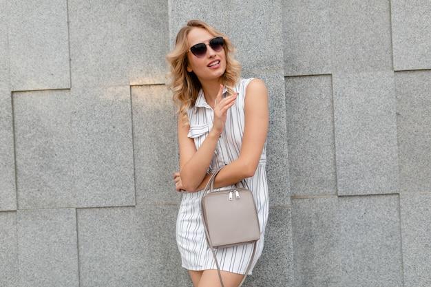 Молодая привлекательная стильная женщина со светлой вьющейся прической гуляет по городской улице в белом полосатом платье в стиле летней моды в темных очках, держа кошелек