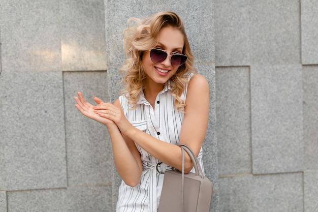 지갑을 들고 선글라스를 착용 여름 패션 스타일 흰색 줄무늬 드레스에 도시 거리에서 걷는 금발 곱슬 헤어 스타일을 가진 젊은 매력적인 세련된 여자