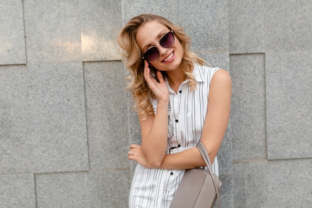 財布を保持しているサングラスを身に着けている夏のファッションスタイルの白い縞模様のドレスで街を歩く金髪の巻き毛の髪型を持つ若い魅力的なスタイリッシュな女性 無料写真
