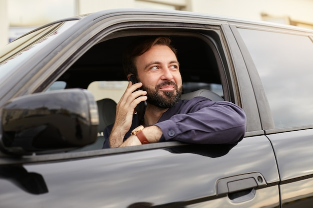 Young attractive successful bearded man in a blue jacket and striped t-shirt, sits behind the wheel of the car, calls on mobile phone, dreamly looks away and smile.