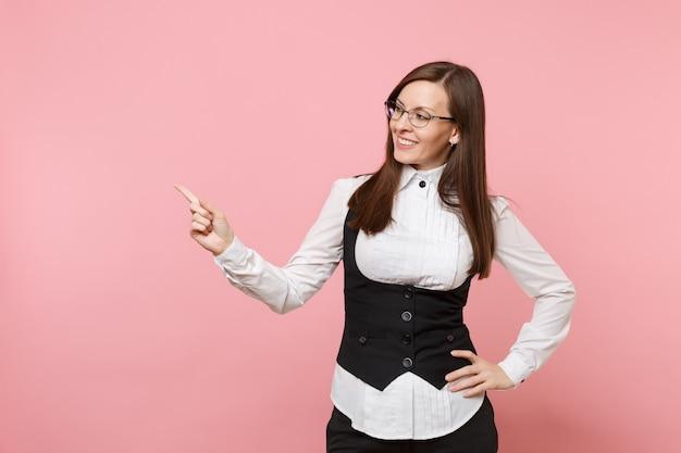 Молодая привлекательная успешная бизнес-леди в очках костюма, указывая указательным пальцем в сторону, изолированную на пастельно-розовом фоне. леди босс. концепция богатства карьеры достижения. скопируйте место для рекламы.