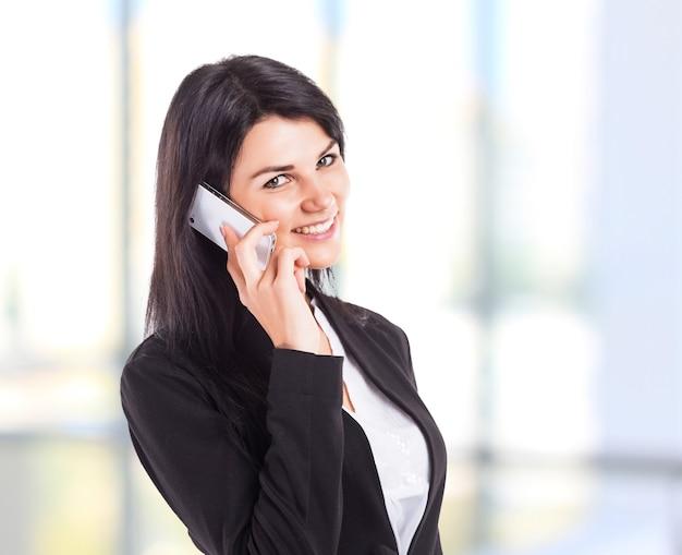 Молодая, привлекательная, успешная деловая женщина разговаривает по телефону.