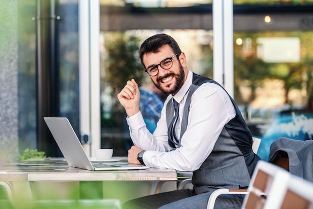 若い魅力的な成功した白人エレガントなひげを生やした実業家眼鏡のカフェに座って、テーブルにもたれて、カメラ目線します。