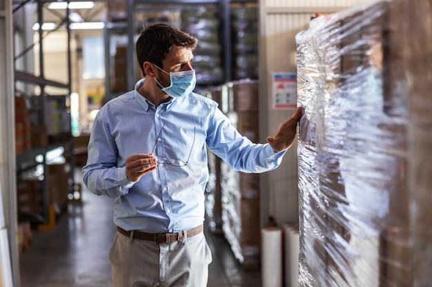Молодой привлекательный руководитель с хирургической маской на складе и проверка товаров. концепция вспышки короны.