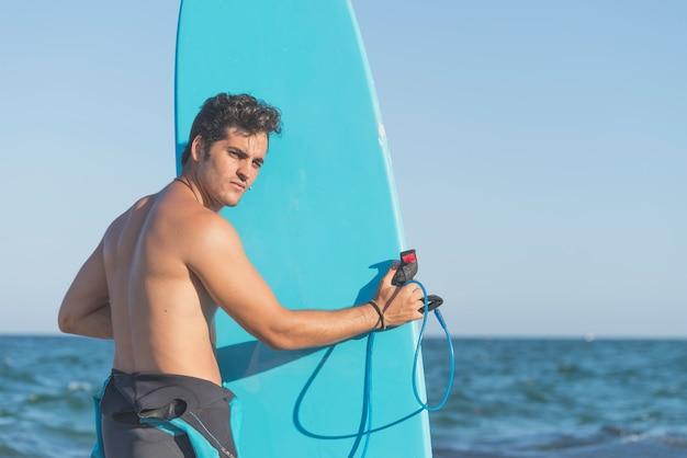 ビーチで彼のサーフボードを持って若い魅力的なサーファー