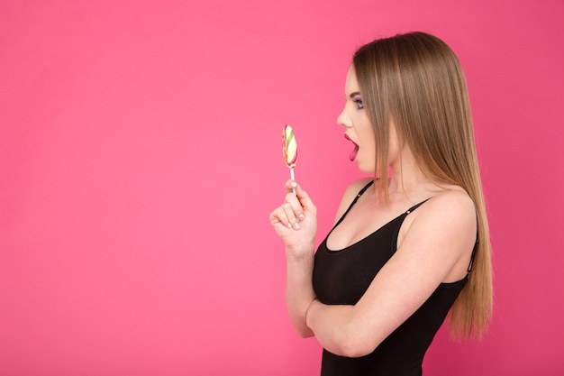 Young attractive surprised pretty excited woman with colorful  lollipop