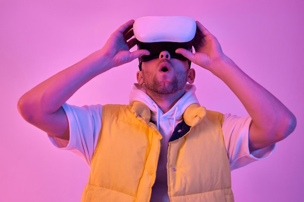 Young attractive surprised shocked man in casual clothes, uses virtual reality glasses isolated on neon pink