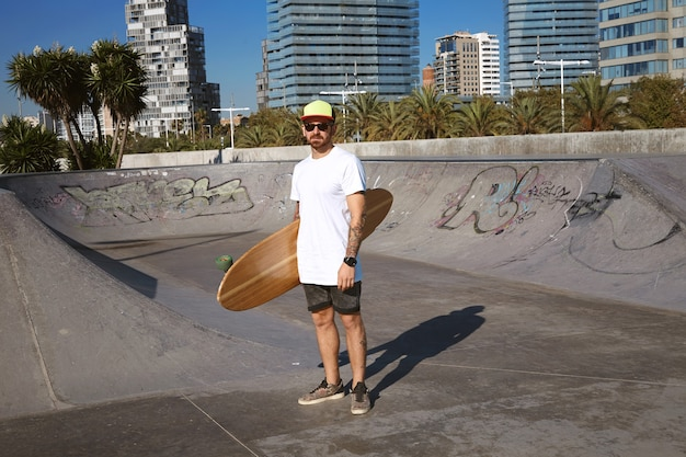 Young attractive tattooed skater in trucker cap stands in unlabeled blank white t-shitrt with his wooden longboard in hand in center of skatepark, urban landscape behind