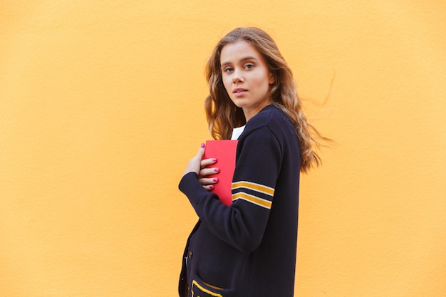 Young attractive teenage girl holding book