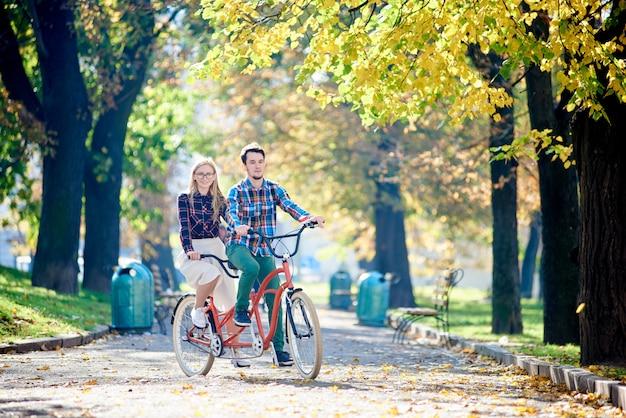 Молодая привлекательная туристическая пара, бородатый человек и белокурая женщина, ездящая на велосипеде на современном тандемном велосипеде на освещенном ярким солнцем пустом тротуаре в красивом осеннем парке под высокими деревьями.