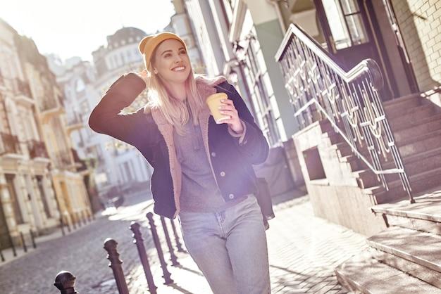 若い魅力的な観光客の女性が路上でコーヒーを飲んでいます