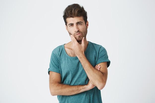 Giovane studente ispanico alla moda attraente in maglietta blu, toccando il viso con la mano guardando pensosamente il programma universitario cercando di scoprire il tempo libero per il lavoro.