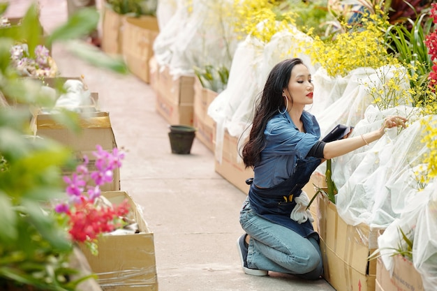 保育園の植物の世話を手にデジタルタブレットを持つ若い魅力的なベトナムの女性