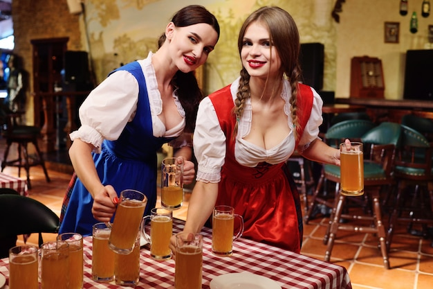 Young attractive waitresses put on the table a lot of glasses or lighter with a light beer on the table.