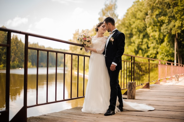 Young and attractive wedding couple on the bridge