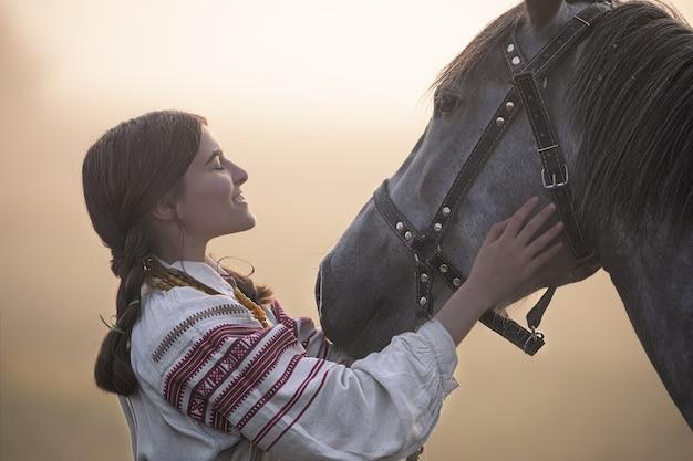 Молодая привлекательная белая женщина в благородной одежде, гладящая лошадь.