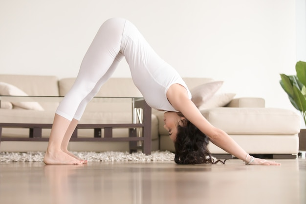 Young attractive woman in adho mukha svanasana pose, living room