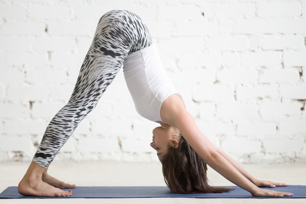 Young attractive woman in adho mukha svanasana pose, white backg