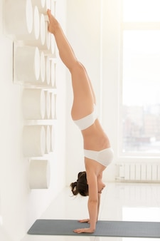 Young attractive woman in adho mukha vrksasana pose, white backg