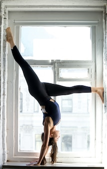 Young attractive woman in adho mukha vrksasana pose, window sill