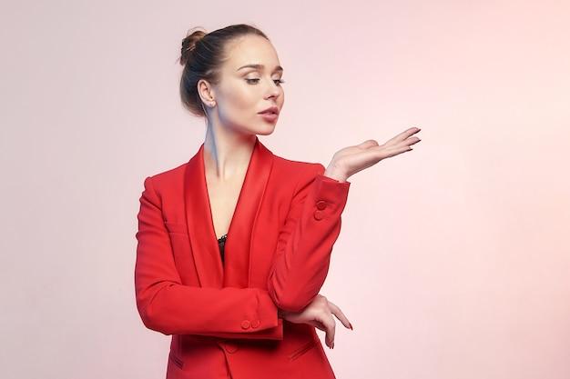 赤いジャケットで彼女の手のひらに保持している何かを宣伝する若い魅力的な女性