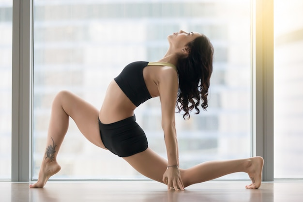 Young attractive woman in anjaneyasana pose against floor window