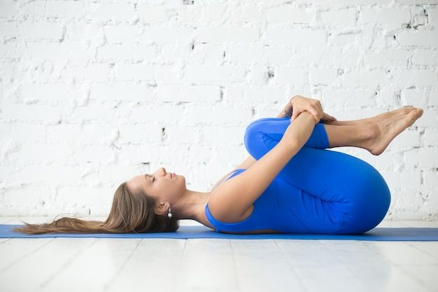 Young attractive woman in apanasana pose, white studio backgroun