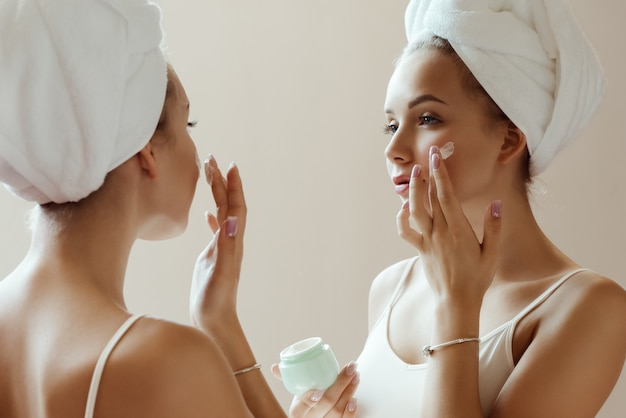 Young attractive woman applying cream to her face while looking at her reflection in the mirror.