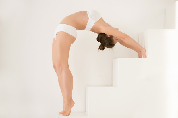 Young attractive woman in ardha chakrasana pose, white color bac