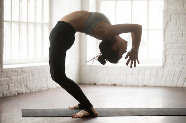 Young attractive woman in ardha chakrasana pose, white loft