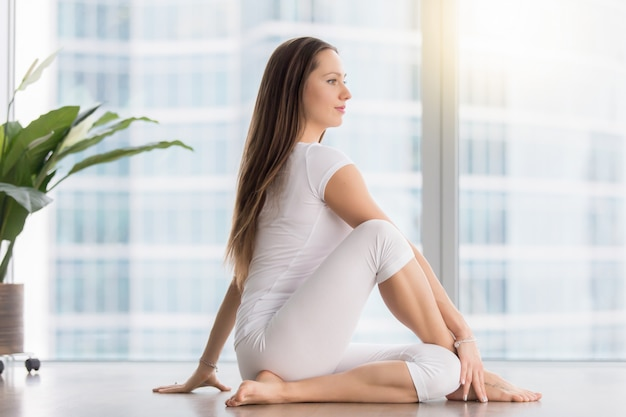 Young attractive woman in ardha matsyendrasana pose against floor window