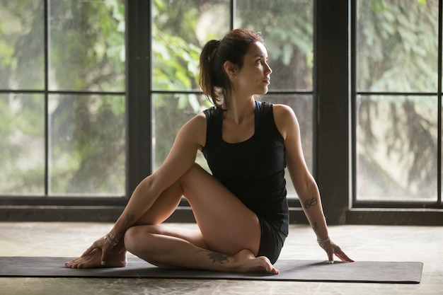 Young attractive woman in ardha matsyendrasana pose
