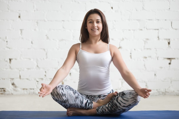 Young attractive woman in ardha padmasana pose, white studio bac