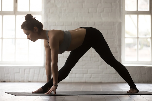 Young attractive woman in ardha parsvottanasana pose