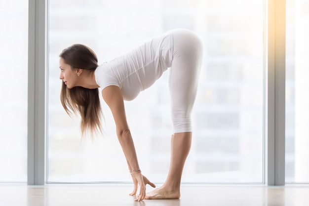 Young attractive woman in ardha uttanasana pose against floor window