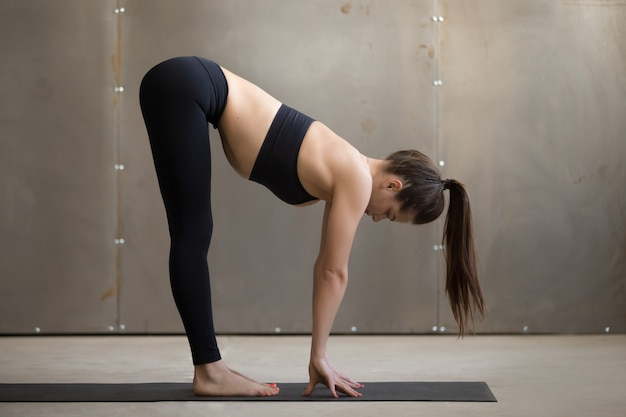 Young attractive woman in ardha uttanasana pose grey studio back