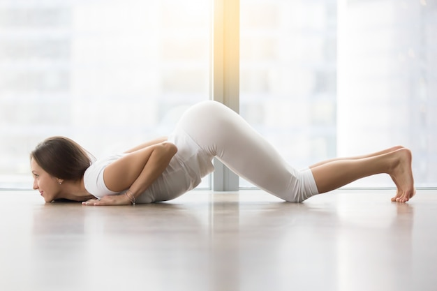 Young attractive woman in ashtanga namaskara pose against floor window