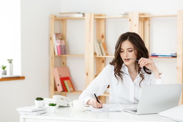 Молодая привлекательная женщина за современным офисным столом работает с ноутбуком и думает о чем-то
