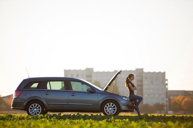 Молодая привлекательная женщина в автомобиле с открытым капотом на зеленом лугу на размытом жилом доме и ясном ярком небе копирует космический фон. транспорт, проблемы с транспортными средствами и концепция поломок.