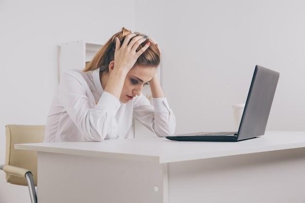 現代のオフィスデスクで若い魅力的な女性、ラップトップで作業し、絶え間ない頭痛を忘れるためにこめかみをマッサージし、片頭痛を与える騒々しい騒々しいオフィス、ストレスを和らげ、慢性的な痛みを和らげるのに役立ちます