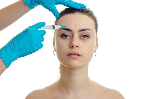 Молодая привлекательная женщина у пластического хирурга изолирована на белой стене