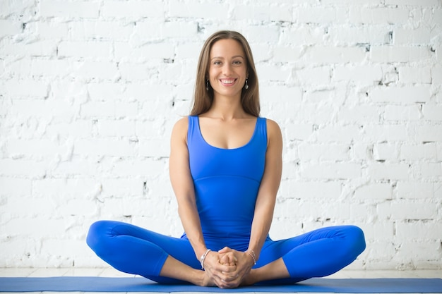 Young attractive woman in baddha konasana pose, white studio bac