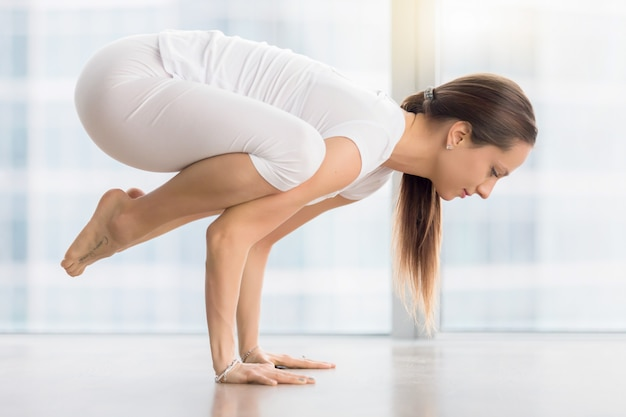 Young attractive woman in bakasana pose against floor window